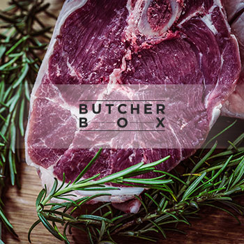 ButcherBox logo, raw meat and green leaf plant on brown surface