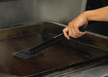 cleaning a dirty grill with a brush