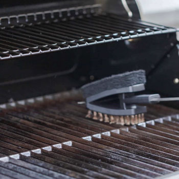 using a brush to clean smoker grills