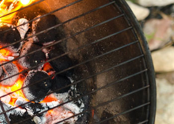 charcoals on fire under cast iron grill grates