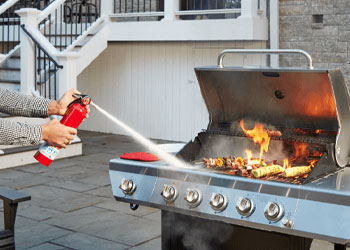 Man putting out a grease fire on a grill