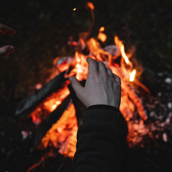 Person starting a fire in a fire pit