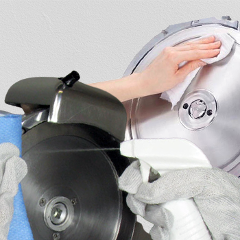 One hand spraying a formula and one hand wiping a meat slicer