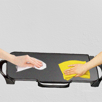 Two hands wiping an electric griddle