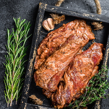 Raw marinated brisket steaks