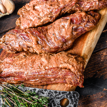 Marinated raw brisket meat on a chopping board